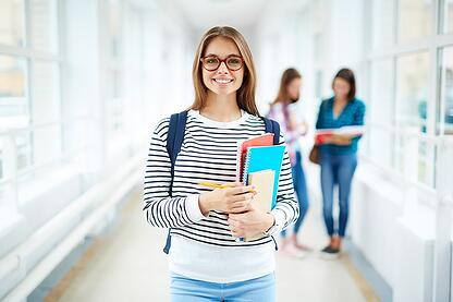 Female college student holding books in hallway