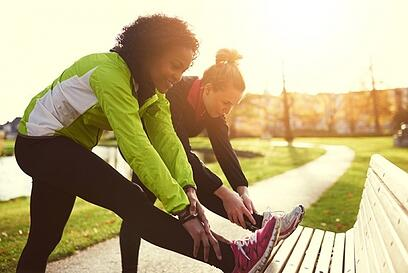 Two women stretching before running