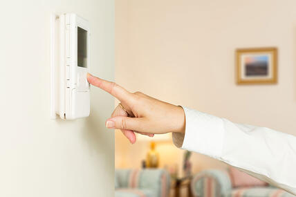 Hand Reaching to Change Thermostat